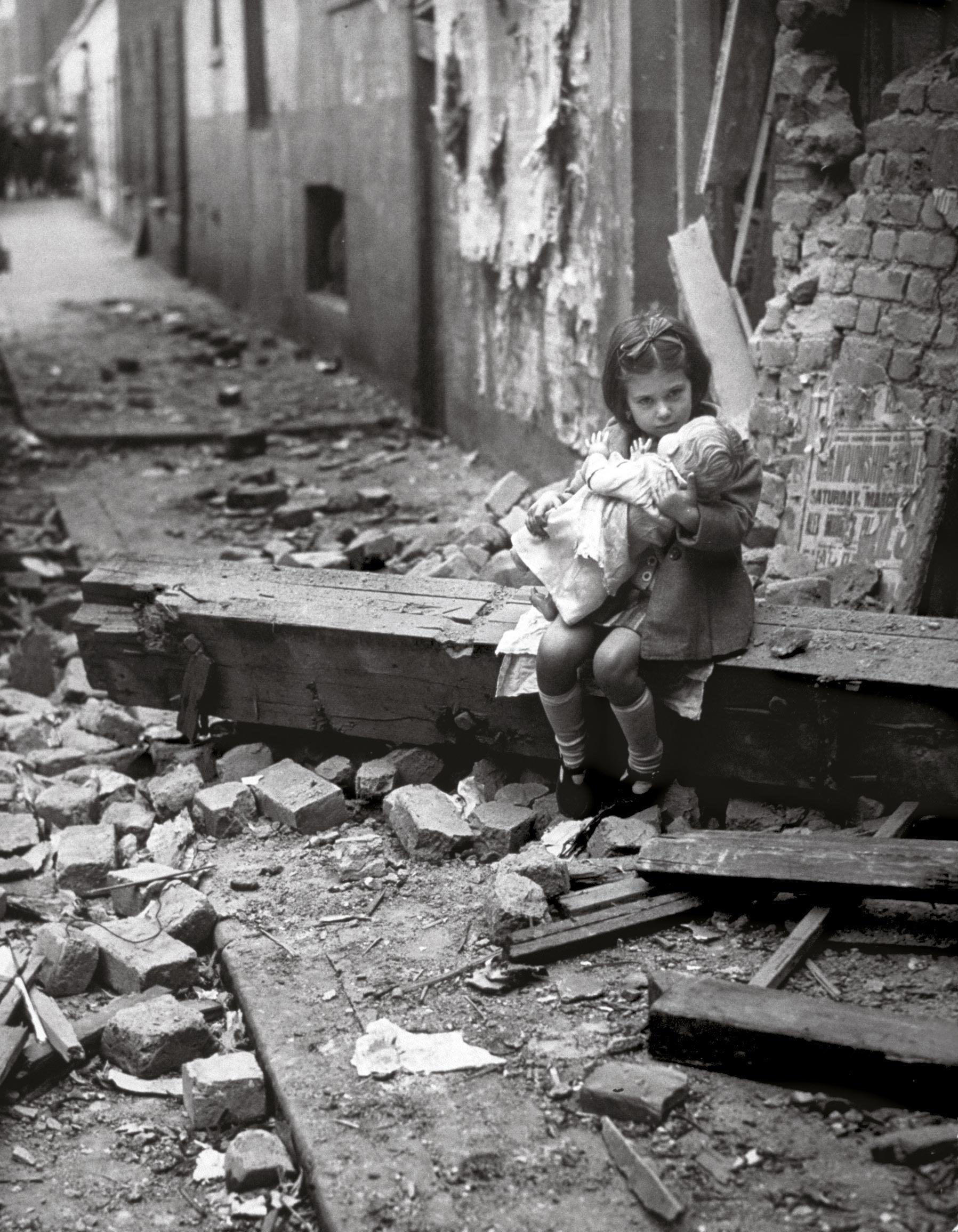 Une petite fille rassure sa poupée dans les décombres de sa maison bombardée