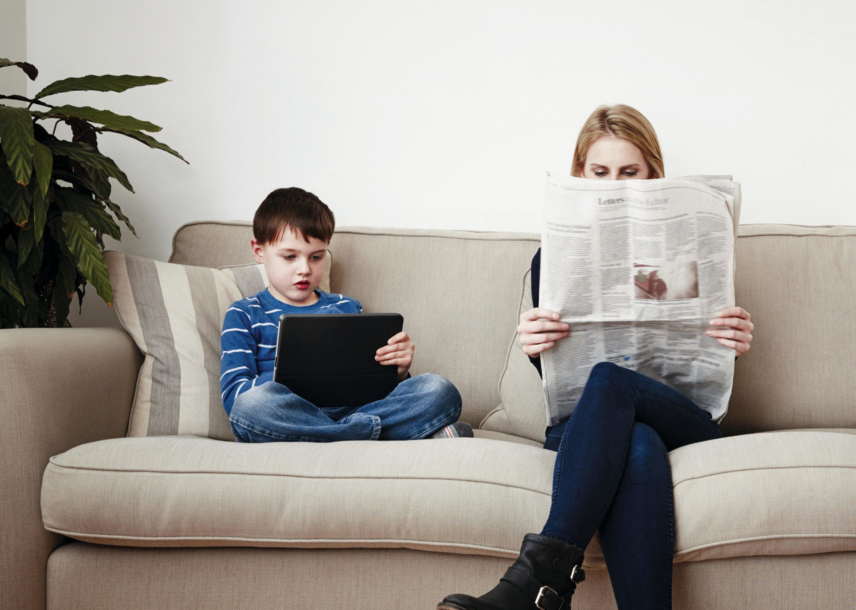 Un jeune garçon utilisant une tablette, une mère lisant le journal