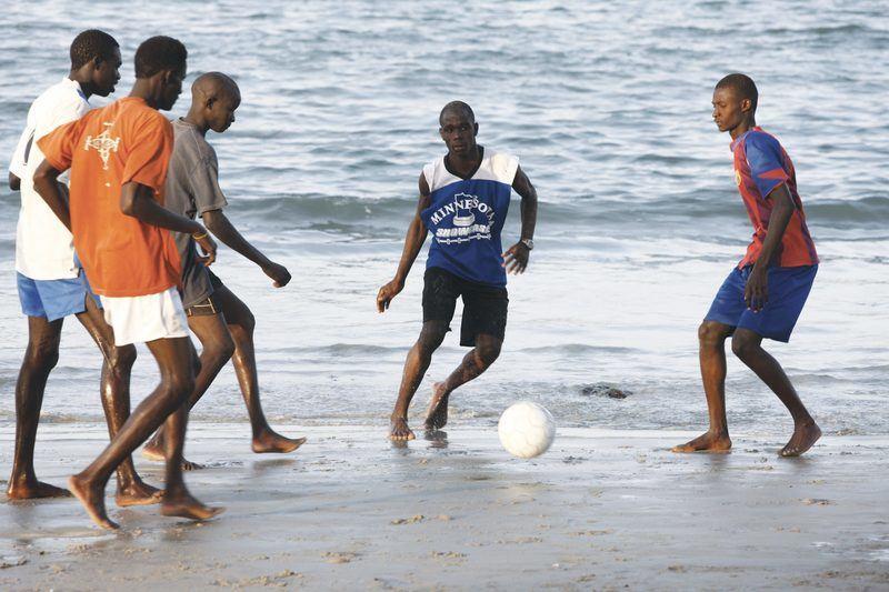 Jeunes gens jouant au football sur la plage de Ngor