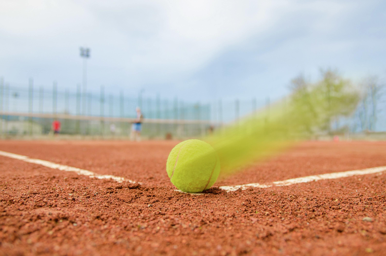 Balle de tennis sur terre battue.