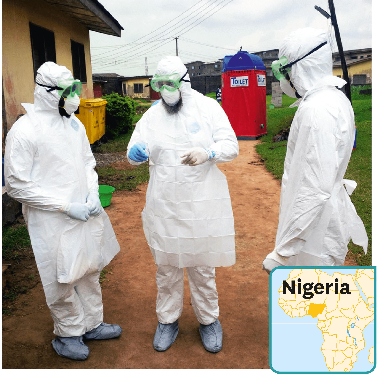 Des médecins portant une combinaison de protection dans une unité de traitement d'Ebola au Nigeria.